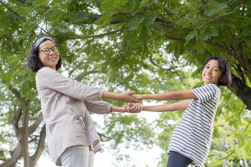 Side view of Asian mother and daughter holding hand and smile while standing in the park, Happy family concept royalty free stock photo