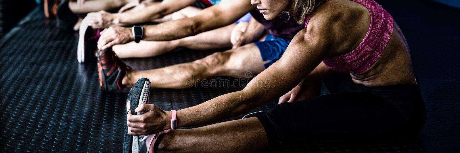 Side view of athletes stretching stock image