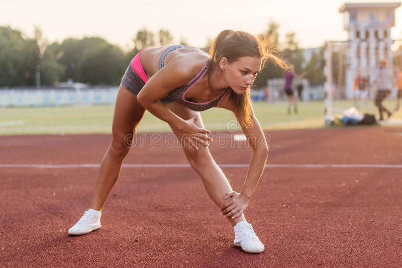 Side view of athletic woman working out on mat in stadium, bending and stretching her back leg muscles stock images