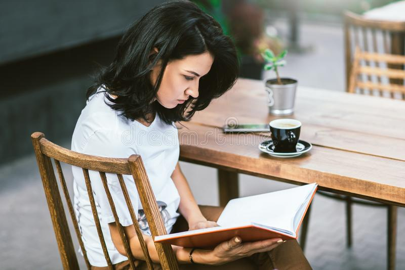 Side view of attractive Caucasian sitting at terrace cafe, drinking coffee and reading book at break time. People, business and stock photo