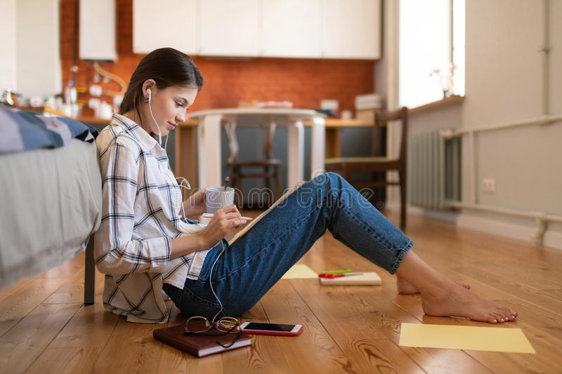 Teenage girl preparing for exam in university. Side view of attractive concentrated teenage female student in earphones sitting on floor preparing for exam at stock photo