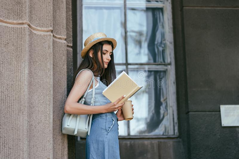 Side view of attractive girl in hat holding coffee to go and reading book. Near column stock photography
