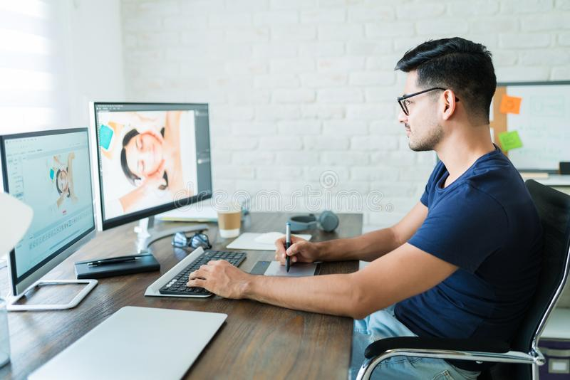 Handsome Young Male Editor Using Graphic Tablet At Desk royalty free stock photo