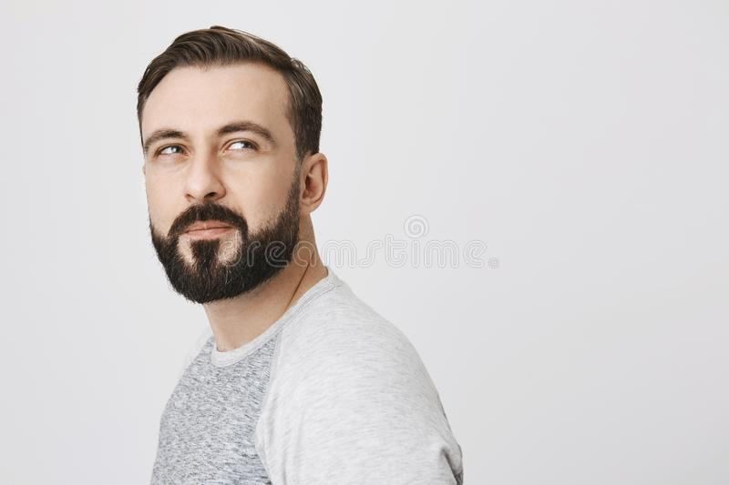 Side view of attractive thoughtful bearded man, turned over to look a something suspiciously, standing against gray stock photo
