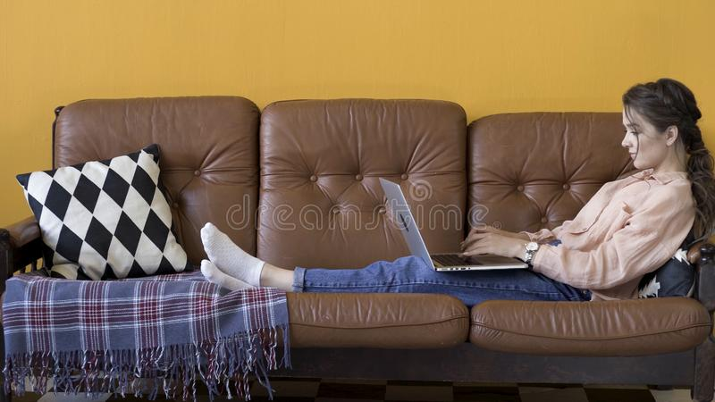 Side view of attractive young brunette woman working on laptop and smiling while sitting on the couch in stylish room. Freelance concept. Female using her royalty free stock photos