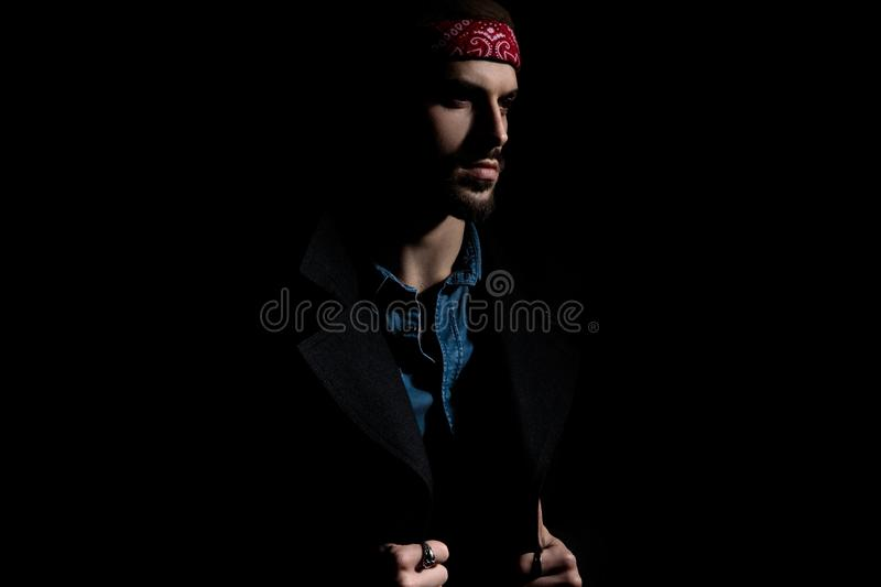 Attractive young man wearing a bandana on black background. Side view of attractive young man wearing a bandana and a long coat, standing on black background royalty free stock photo