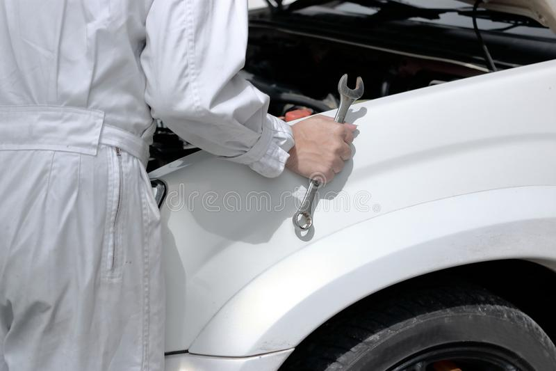 Side view of automotive mechanic in uniform with wrench diagnosing engine under hood of car at the repair garage. royalty free stock photo