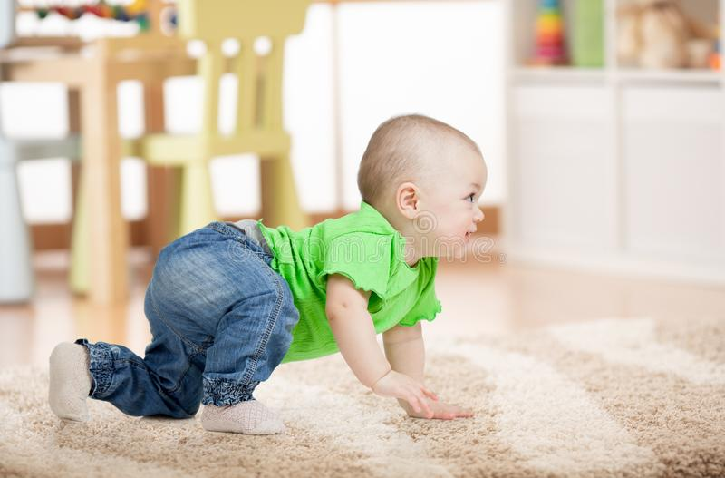 Side view of baby crawling on carpet on floor in children room. Side view of baby crawling on soft carpet on floor in children room royalty free stock photos