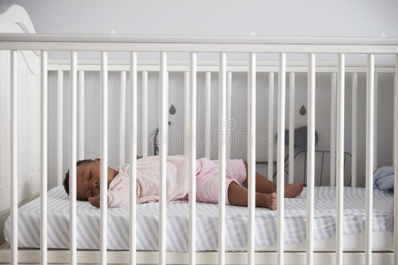 Side View Of Baby Girl Sleeping In Nursery Cot stock image