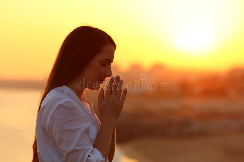 Side view of a woman praying at sunset stock photo