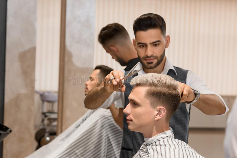 Barber concentrated on shaving man`s beard using sharp razor. stock image