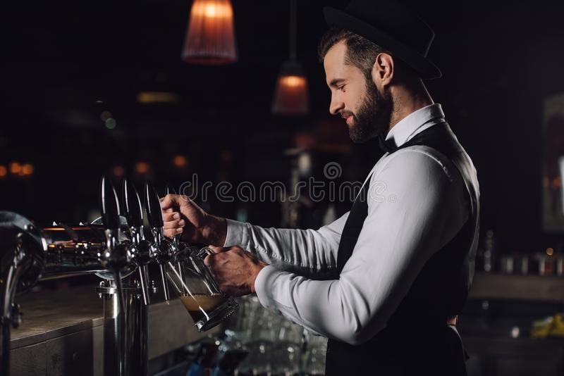side view of bartender pouring beer from beer taps stock images