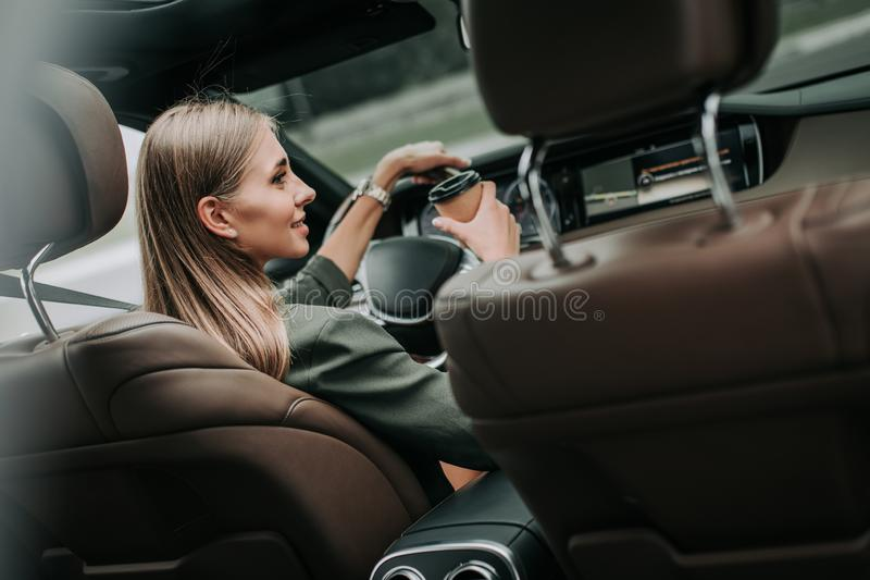 Pleased woman tasting liquid in the auto royalty free stock image