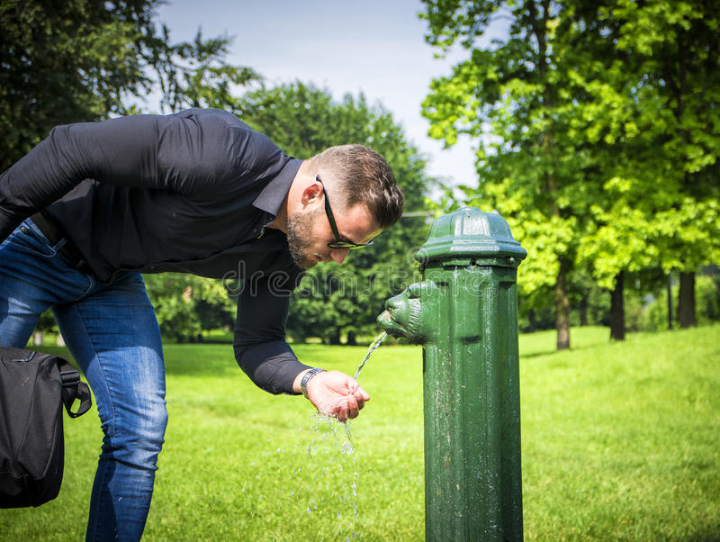 Side view of bearded businessman drinking water from park fountain stock images