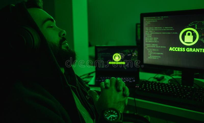 Bearded hacker relaxing near computer. Side view of bearded man in hoodie clasping hands and keeping eyes closed while sitting near computer after successful stock images