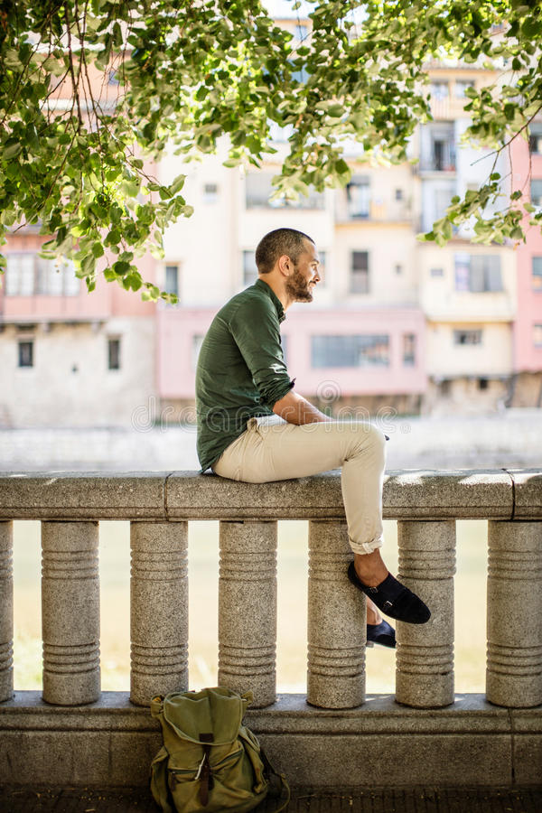 Side view of bearded man sitting on fence under trees stock photography