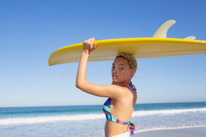 Beautiful woman in bikini carrying the surfboard on her head at beach in the sunshine. Side view of beautiful African american woman in bikini carrying the stock images