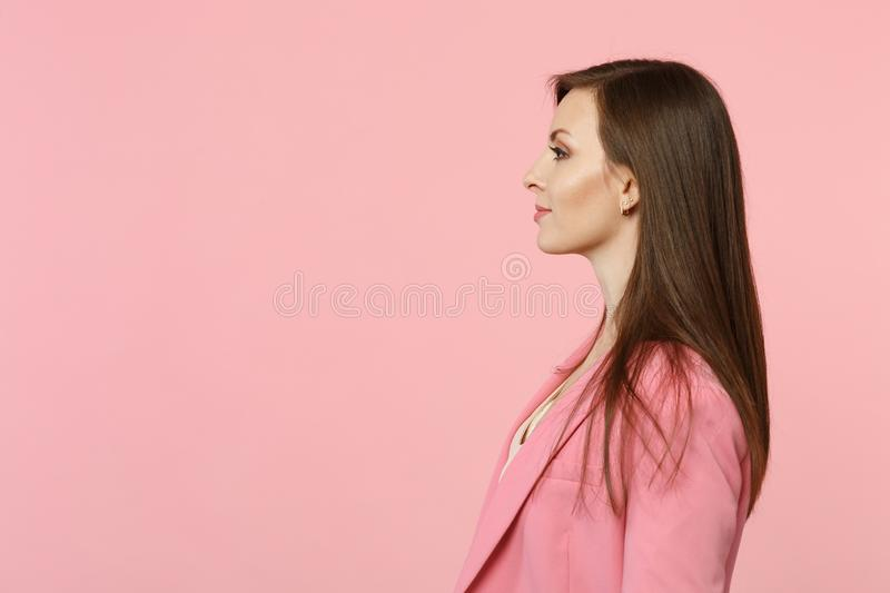 Side view of beautiful attractive smiling young woman wearing jacket looking aside isolated on pastel pink wall stock photography