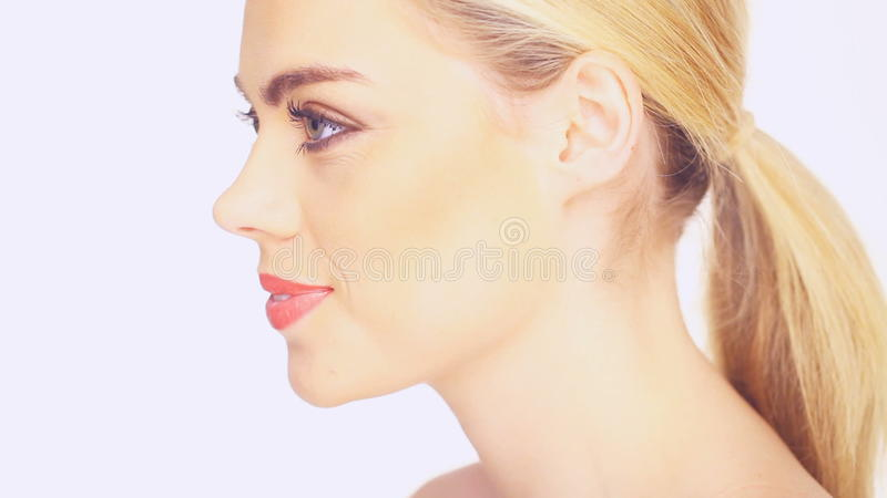 Side view of a beautiful blond woman. With her long hair in a ponytail and a gentle smile, isolated on white stock video