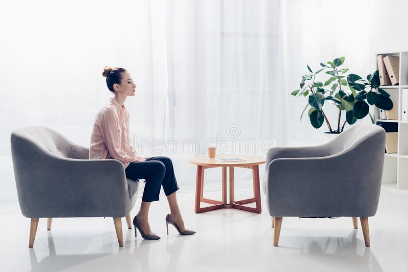Side view of beautiful businesswoman sitting in armchair in office and. Looking away royalty free stock photo
