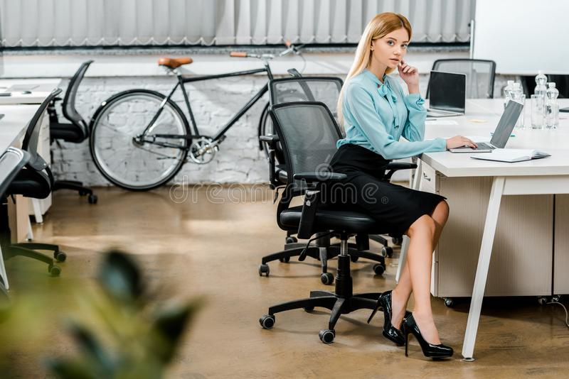 Side view of beautiful businesswoman sitting at workplace with laptop and notebook in office. With bicycle stock photography
