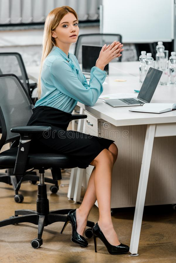 Side view of beautiful businesswoman sitting at workplace. With laptop and notebook stock images