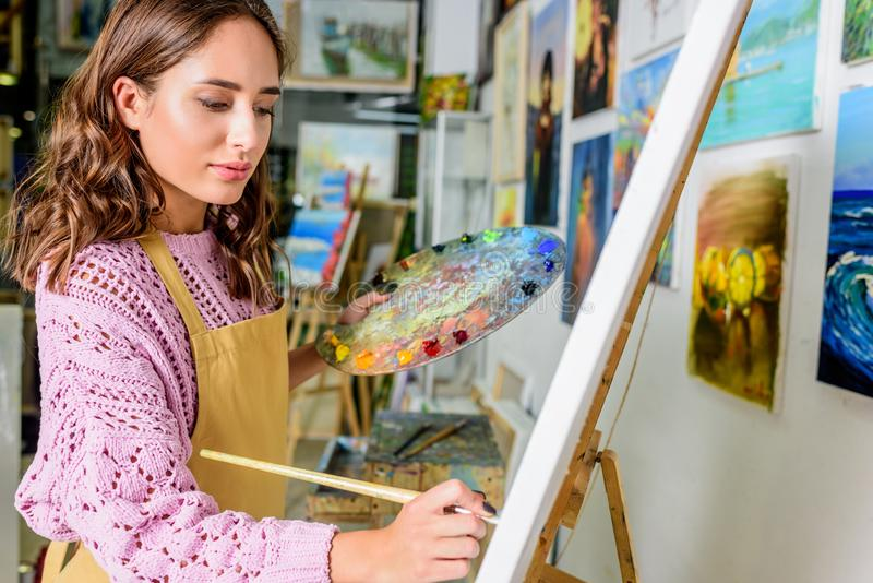 Side view of beautiful female artist painting on canvas. In workshop royalty free stock photography