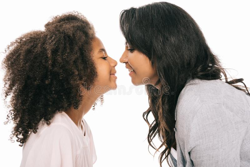 side view of beautiful happy african american mother and daughter smiling each other stock photo