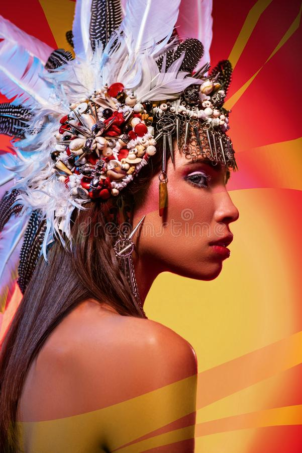 Side view of beautiful naked woman in tribal headdress stock images