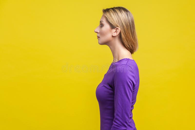 Side view of beautiful serious woman in elegant purple dress showing her neck. isolated on yellow background royalty free stock images