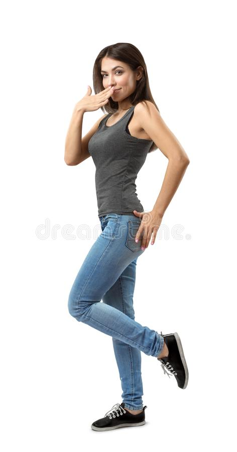Side view of beautiful woman in gray top and blue jeans standing with one hand covering mouth and one knee bent and foot stock image