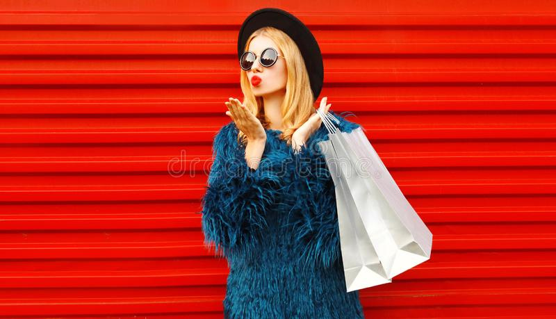 Side view beautiful woman with shopping bags blowing red lips sending sweet air kiss, stylish female model royalty free stock photo