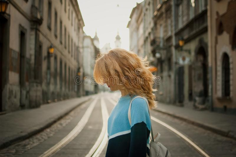 Side view of beautiful young adult girl tourist enjoying her trip early in the morning in empty city in Europe on street royalty free stock images