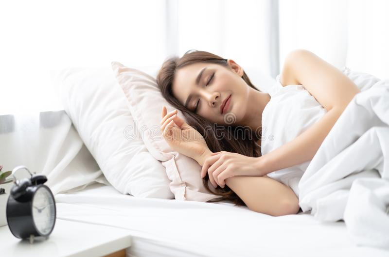 Side view of beautiful young Asian woman smiling while sleeping in her bed and relaxing in the morning. Lady enjoying sweet dreams royalty free stock image