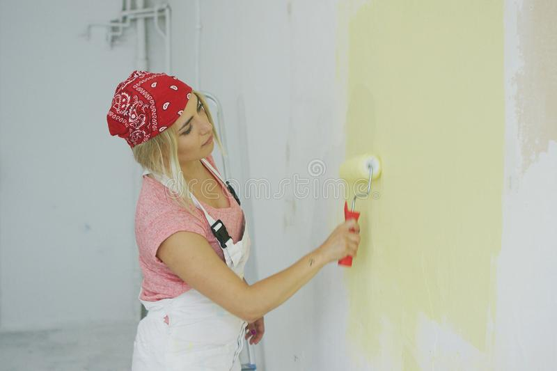 Woman painting wall with roller royalty free stock image