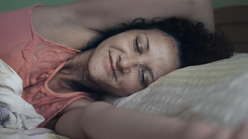 Side view of beautiful young Hispanic woman smiling while sleeping in her bed stock image