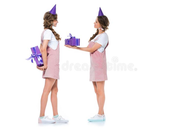 side view of beautiful young twins gifting each other presents royalty free stock photos