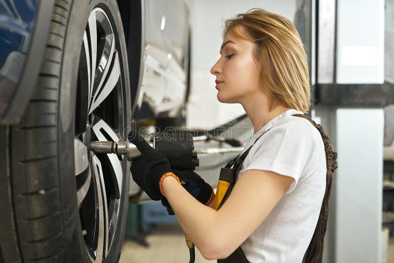 Young woman repairing automobile hubcap, using tool. Side view of beautiful young woman repairing hubcap of wheel, holding tool. Pretty girl, professional royalty free stock photos