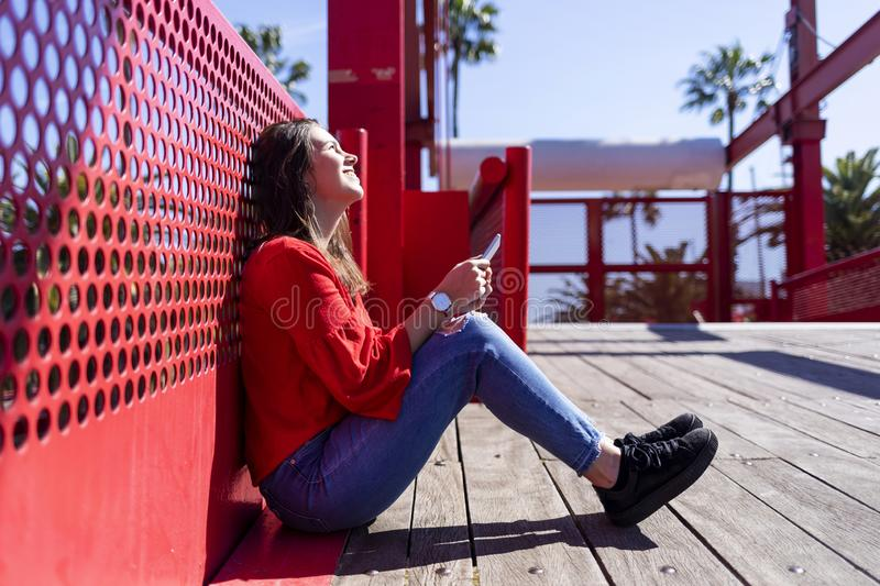 Front view of a beautiful young woman wearing urban clothes sitting on a metallic fence while using a mobile phone outdoors in the stock photography