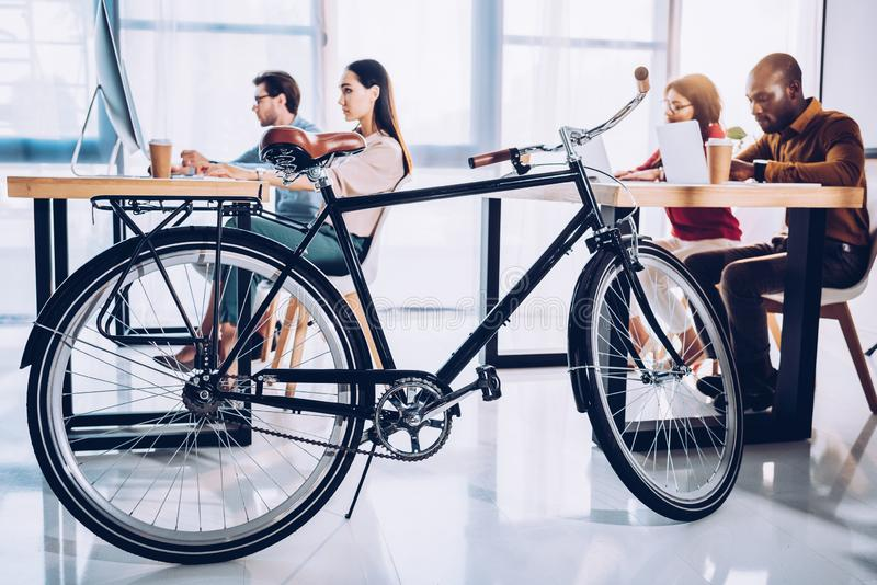 side view of bicycle and multicultural business people working royalty free stock image