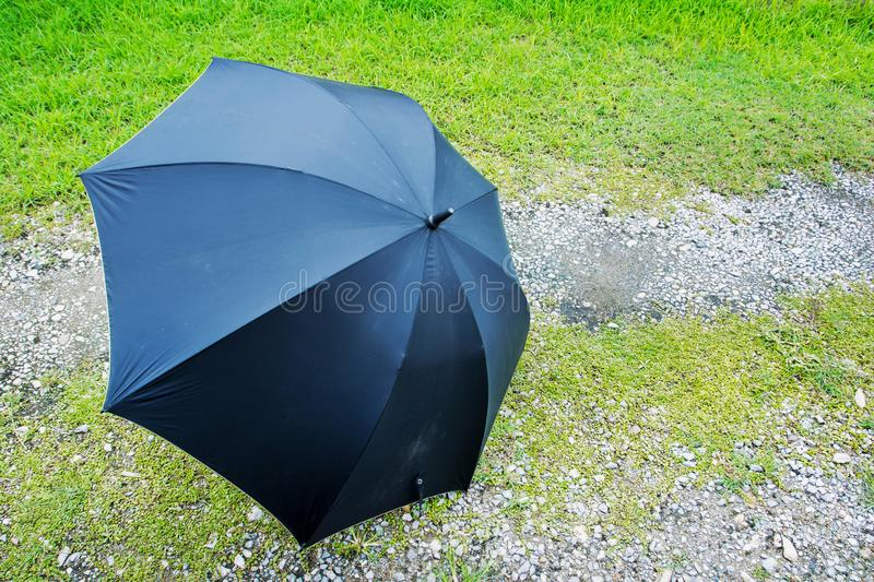 Side view of black umbrella place on grass background. Opened big black umbrella on grass stock photography