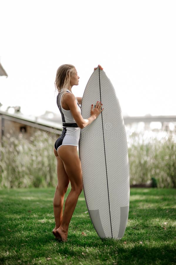 Side view blonde girl standing with the wakeboard. Side view blonde girl in black and white swimsuit standing with the wakeboard on the blurred background of old stock photo