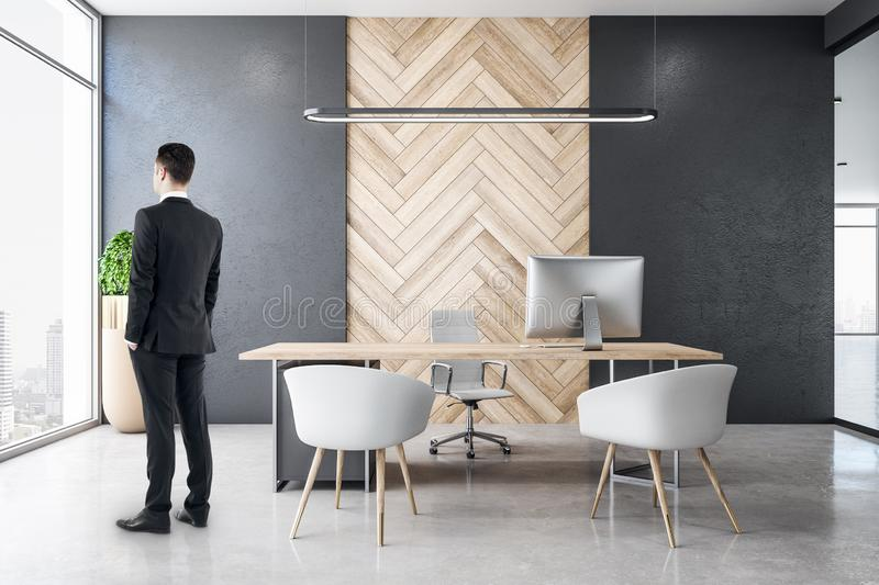 Businessman in modern office. Side view of blurry businessman standing in modern spacious office room interior with city view and daylight. Executive and royalty free stock photography