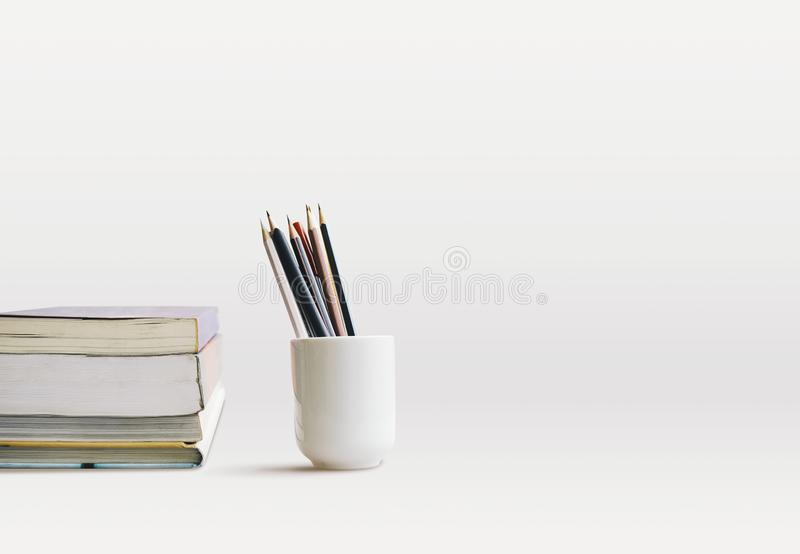 Side view of books stacking and cup of pencils, pens on the desk with copy space. Reading concept. A white cup of pencils, pens and books stacking on the white royalty free stock photos