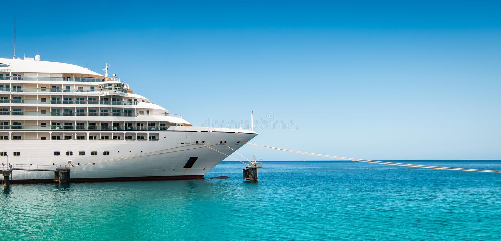 Side view and bow of a docked cruise ship on a summer day with clear blue sky royalty free stock photo