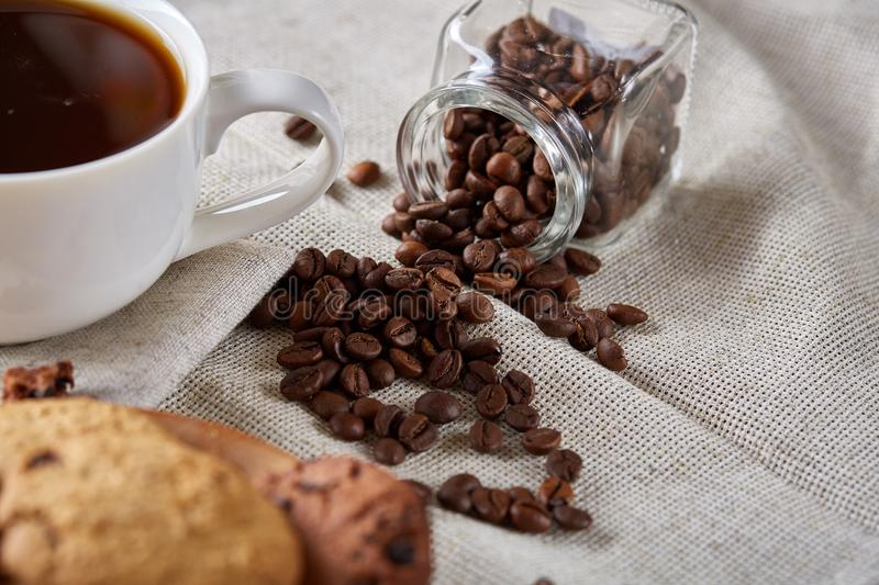 Coffee cup, jar with coffee beans, cookies over homespun tablecloth, selective focus, close-up, side view. Side view breakfast still life with coffee cup royalty free stock images