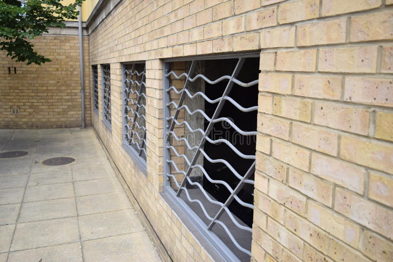 Side view of a brick wall with sliver bars. Silver bars enclosing underground car park royalty free stock photography