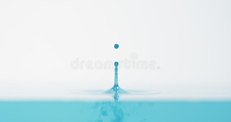Side view of bright blue water drop with accurate splash stock images