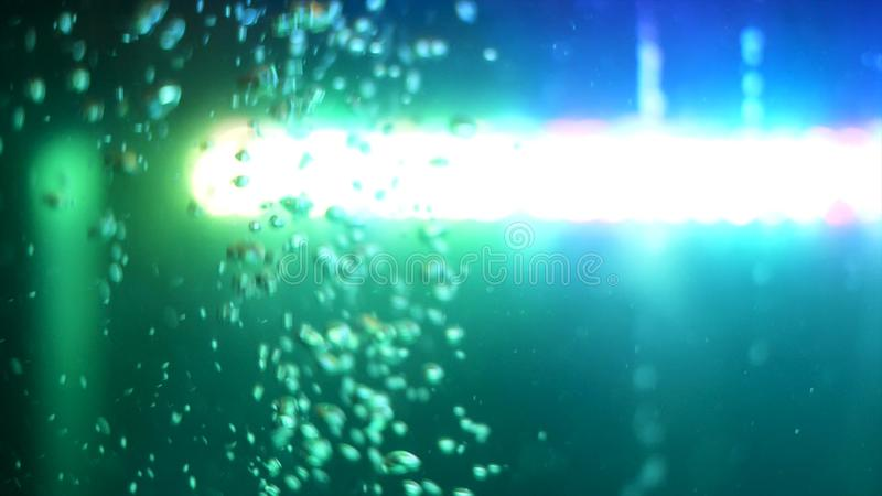 Side view of bubbling water with a green lamp on the background. Frame. Air bubbles underwater in empty fish aquarium. Side view of bubbling water with a green stock image