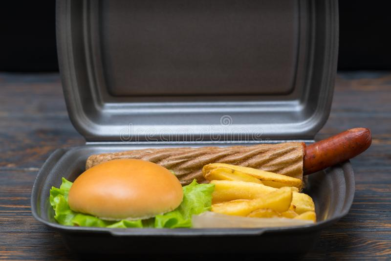 Side view of burger next to potato slices royalty free stock image
